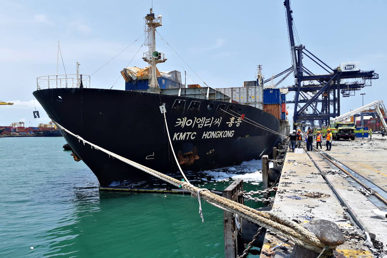 Officials on Tuesday test the water around the HTMC Hongkong cargo ship which carried containers that exploded injuring 133 people on Saturday. (Photo by Pollution Control Department)