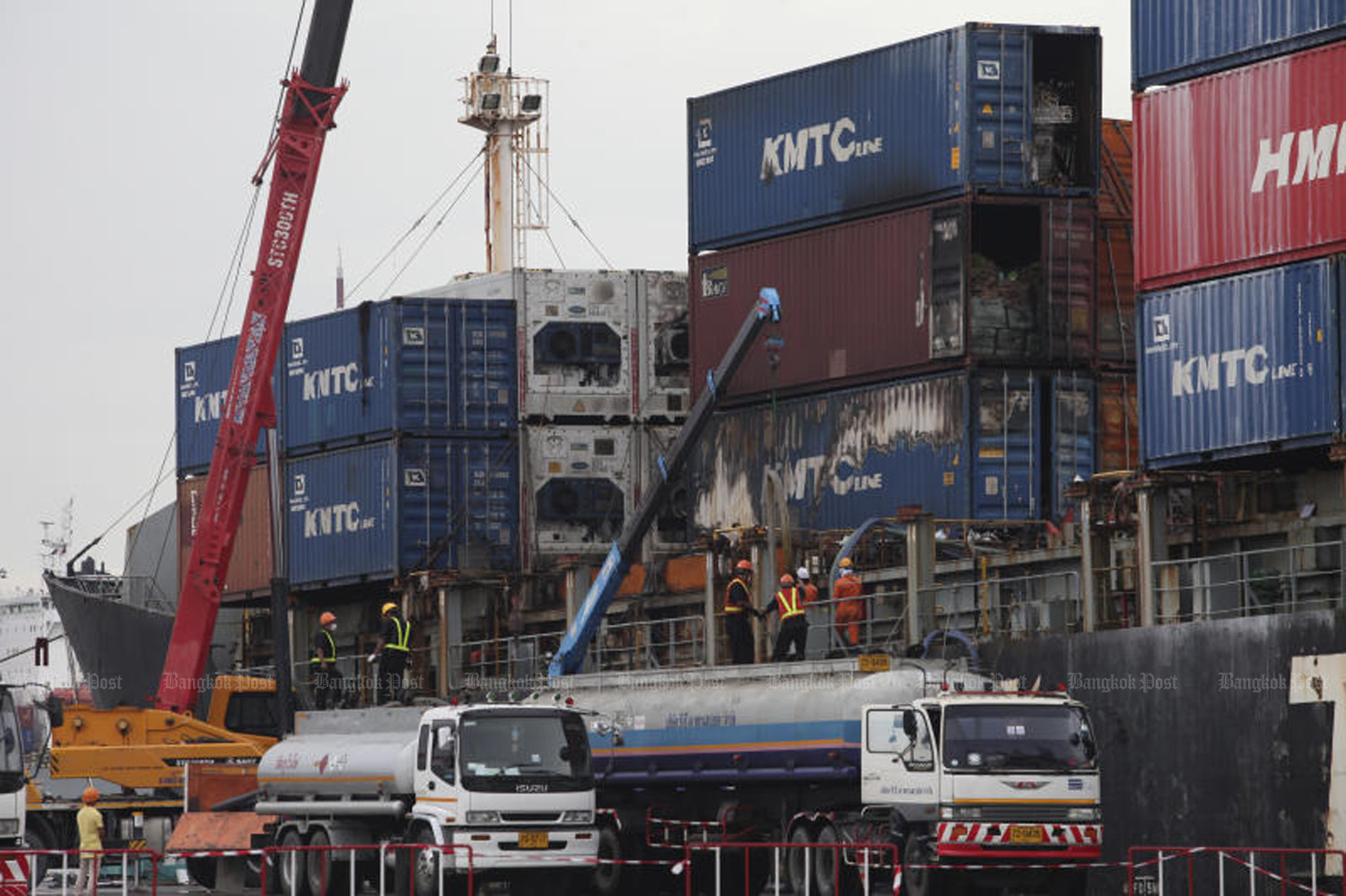 SCENE OF THE BLAZE: Port officials inspect the fire-damaged containers on board the 'KMTC Hong Kong' vessel berthed at Laem Chabang Port in Chon Buri's Sri Racha district. On the morning of May 25, a fire broke aboard the ship carrying containers loaded with chemicals. (Photo by Apichart Jinakul)