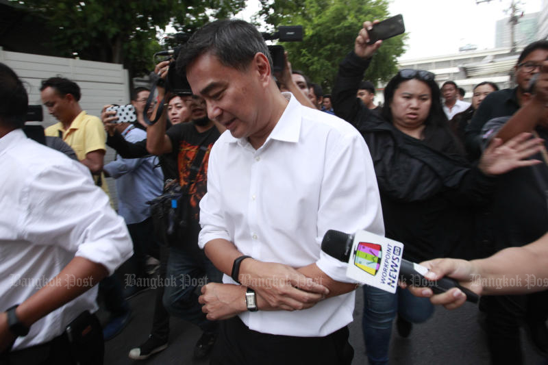 Former Democrat leader Abhisit Vejjajiva is surrounded by reporters as he leaves the party offices after a meeting between its executive and MPs was abruptly adjourned On May 28 before it decided whether to officially join a Palang Pracharath-led coalition.
