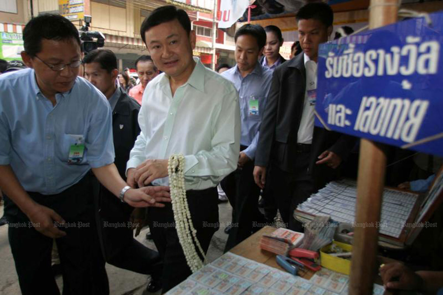 Then-prime minister Thaksin Shinawatra walks past a government lottery stall in Tak province in 2004. (File photo by Chanat Katanyu)