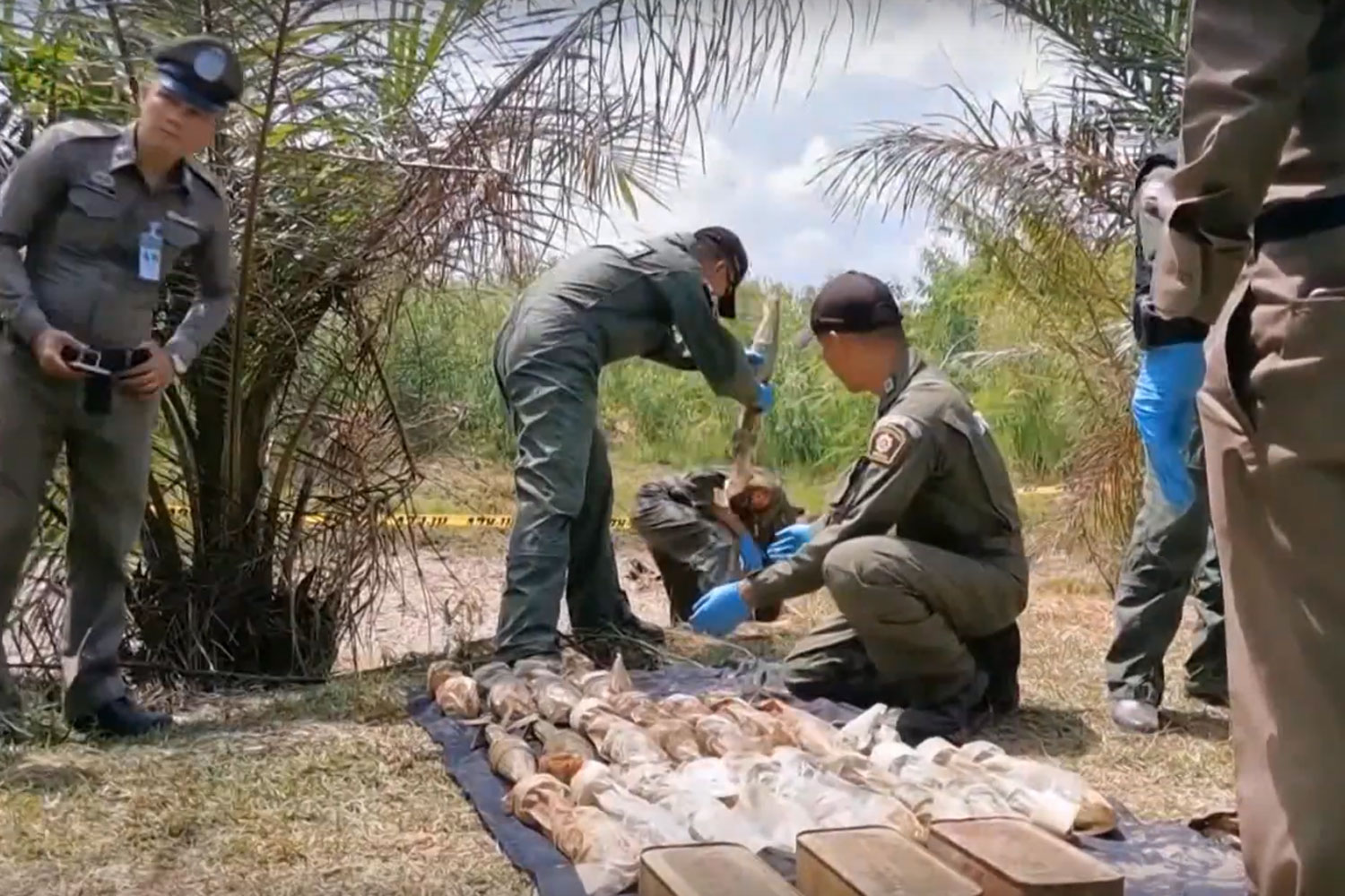 In this screehshot from a TV report of the National Broadcasting Services of Thailand, police check weapons found in a canal in Khukhan district of Si Sa Ket province on Thursday.