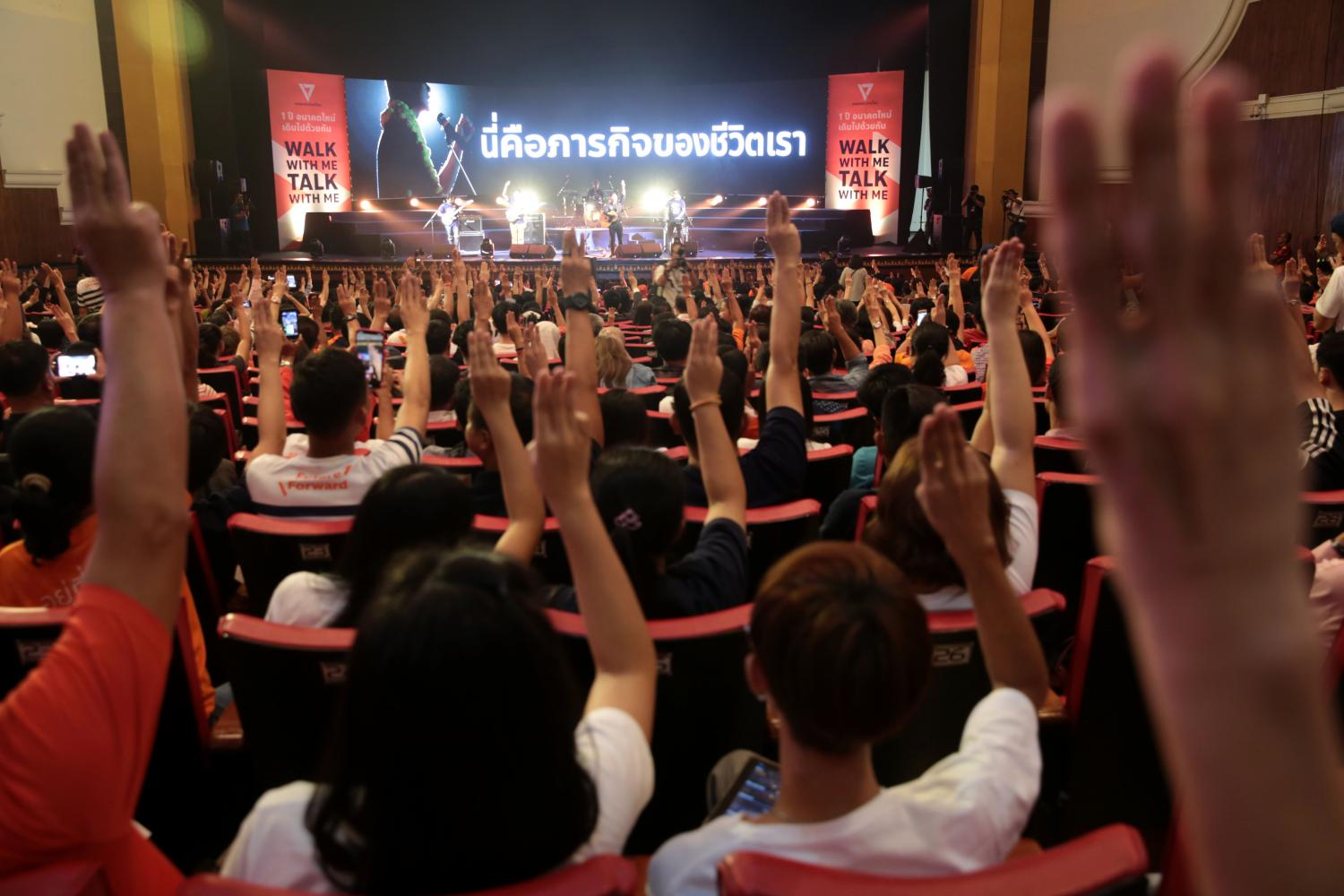 Supporters of the Future Forward Party on Saturday flash a three-finger salute inside a hall at Thammasat University's Tha Prachan campus, where the party organised an event to mark the first anniversary of its founding. (Photo by Chanat Katanyu)