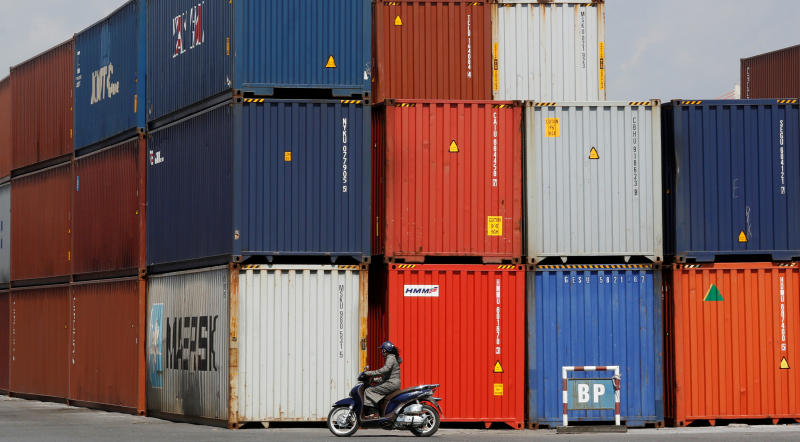 A woman rides a motorcycle as she passes containers at Hai Phong port, Vietnam on Sept 25, 2018. (Reuters file photo)