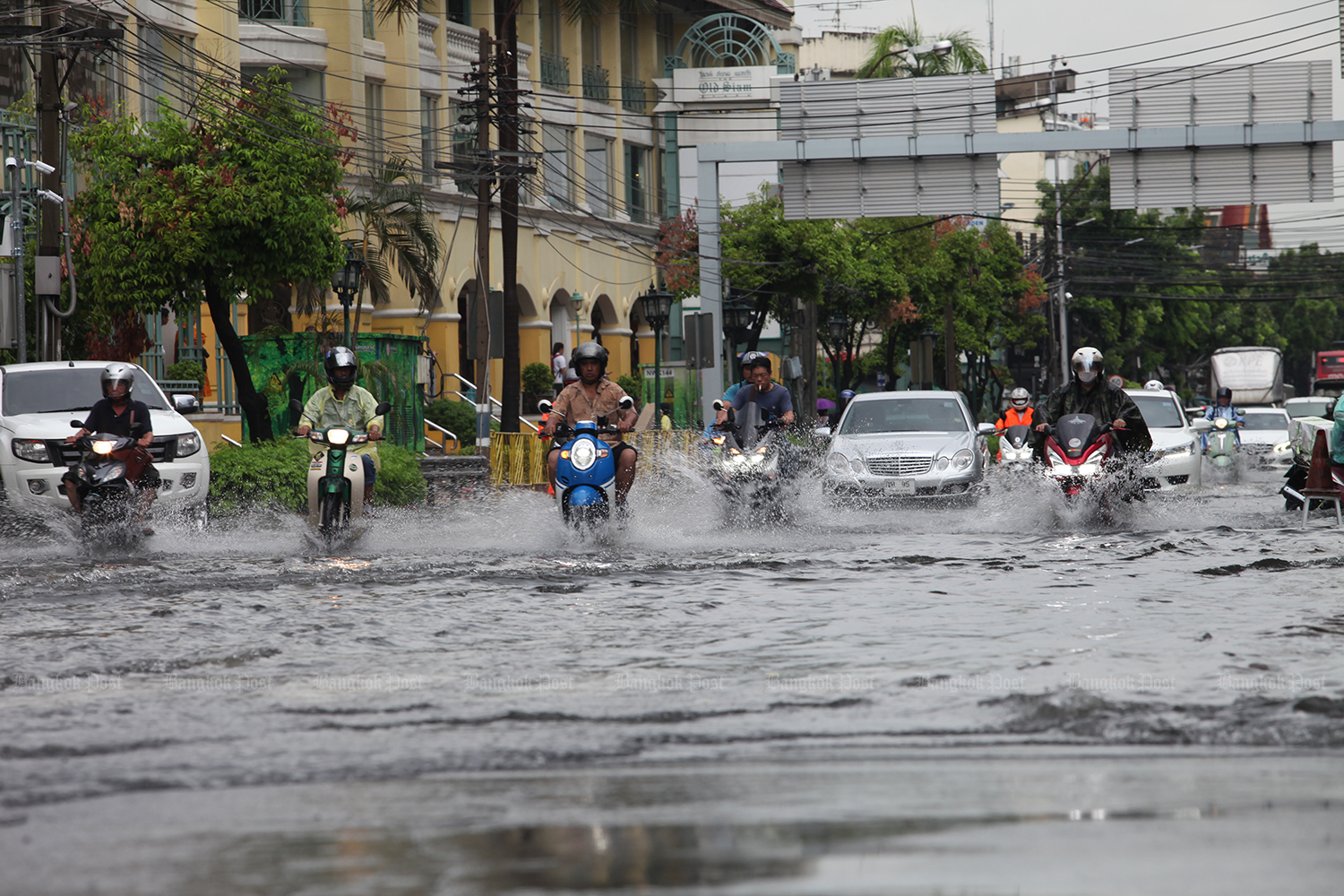 Motorists on Tri Petch Road fight floodwater after a downpour in Bangkok on Friday. (Photo by Apichart Jinakul)
