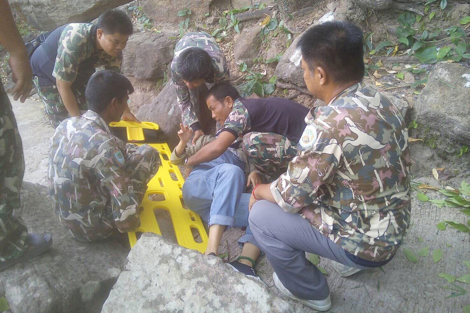 Park rangers help a pregnant Chinese woman who fell from a cliff at the Pha Taem National Park in Khong Chiam district of Ubon Ratchathani province on Sunday morning. (Photo from the Pha Taem National Park)