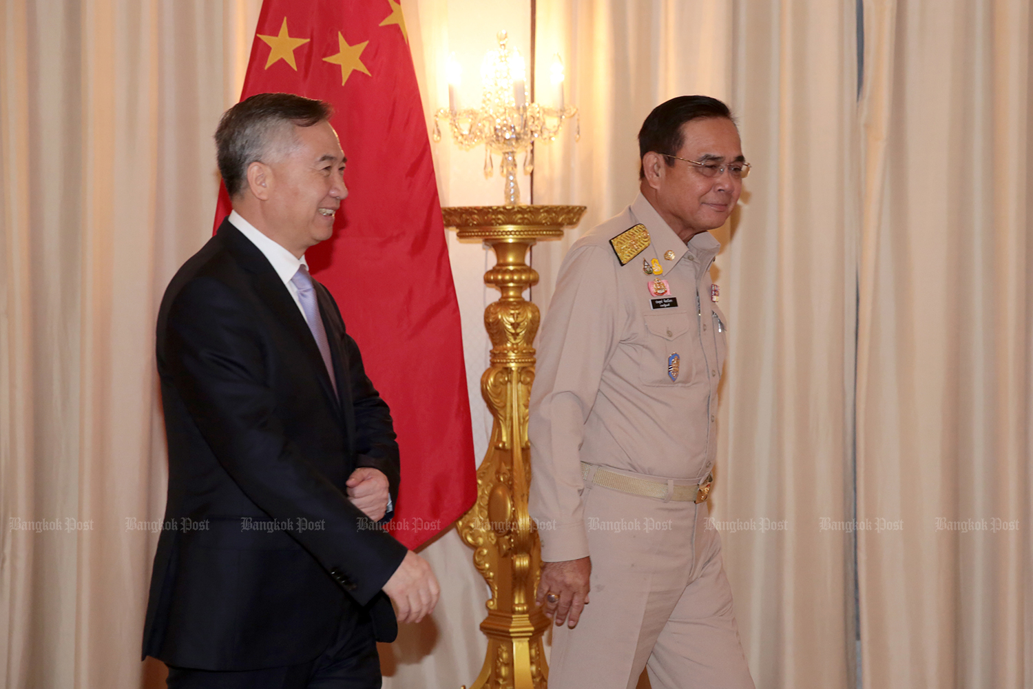 Prime Minister Prayut Chan-o-cha accompanies Guangdong governor Li Xi to a meeting room  at Government House on Monday. (Photo by Chanat Katanyu)