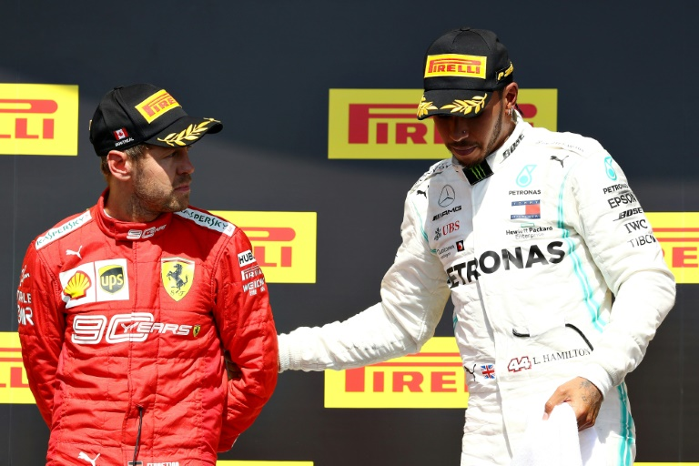 Lewis Hamilton pulls Sebastian Vettel on to the top step of the podium after the Canadian GP
