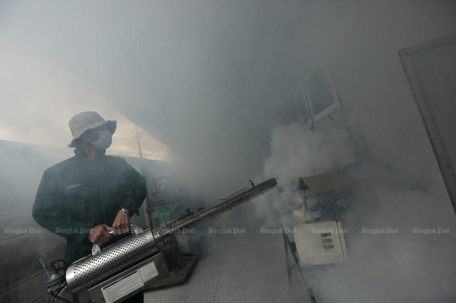 A Wang Thonglang district official sprays fogging chemicals in a residential area  in Soi Lat Phrao 69 on Lat Phrao Road in Bangkok to prevent the spread of mosquitoes that cause dengue fever. (File photo by Patipat Janthong)