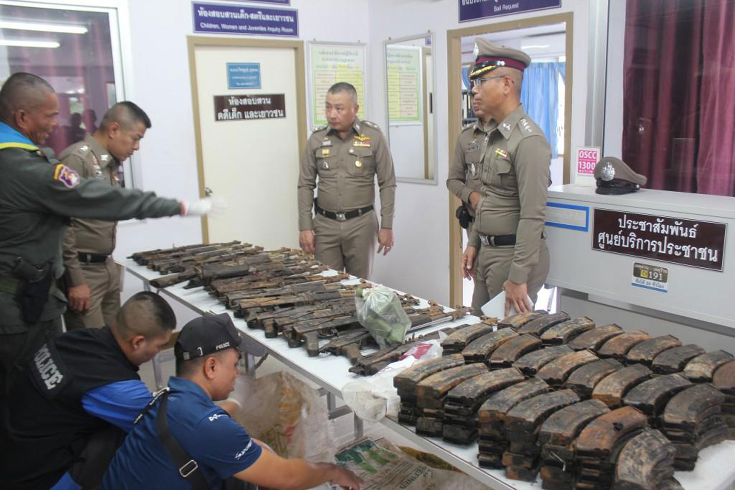 Police examine a cache of AKA assault rifles and magazines at the Phu Sing police station in Surin province on Monday. (Photo by Noparat Kingkaew)