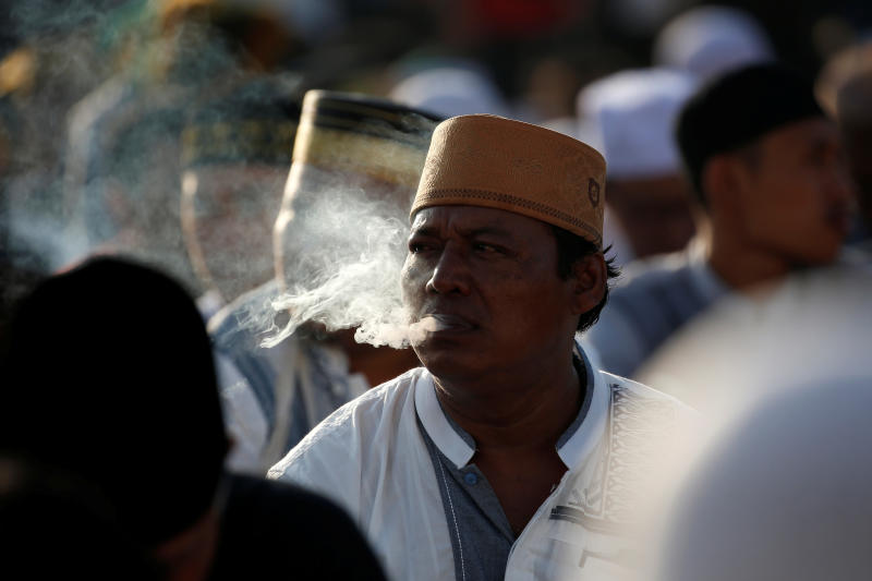 A man smokes cigarette as he attends morning prayers to celebrate Eid al-Fitr, marking the end of the holy fasting month of Ramadan, at Sunda Kelapa port in Jakarta on June 5, 2019. (Reuters photo)