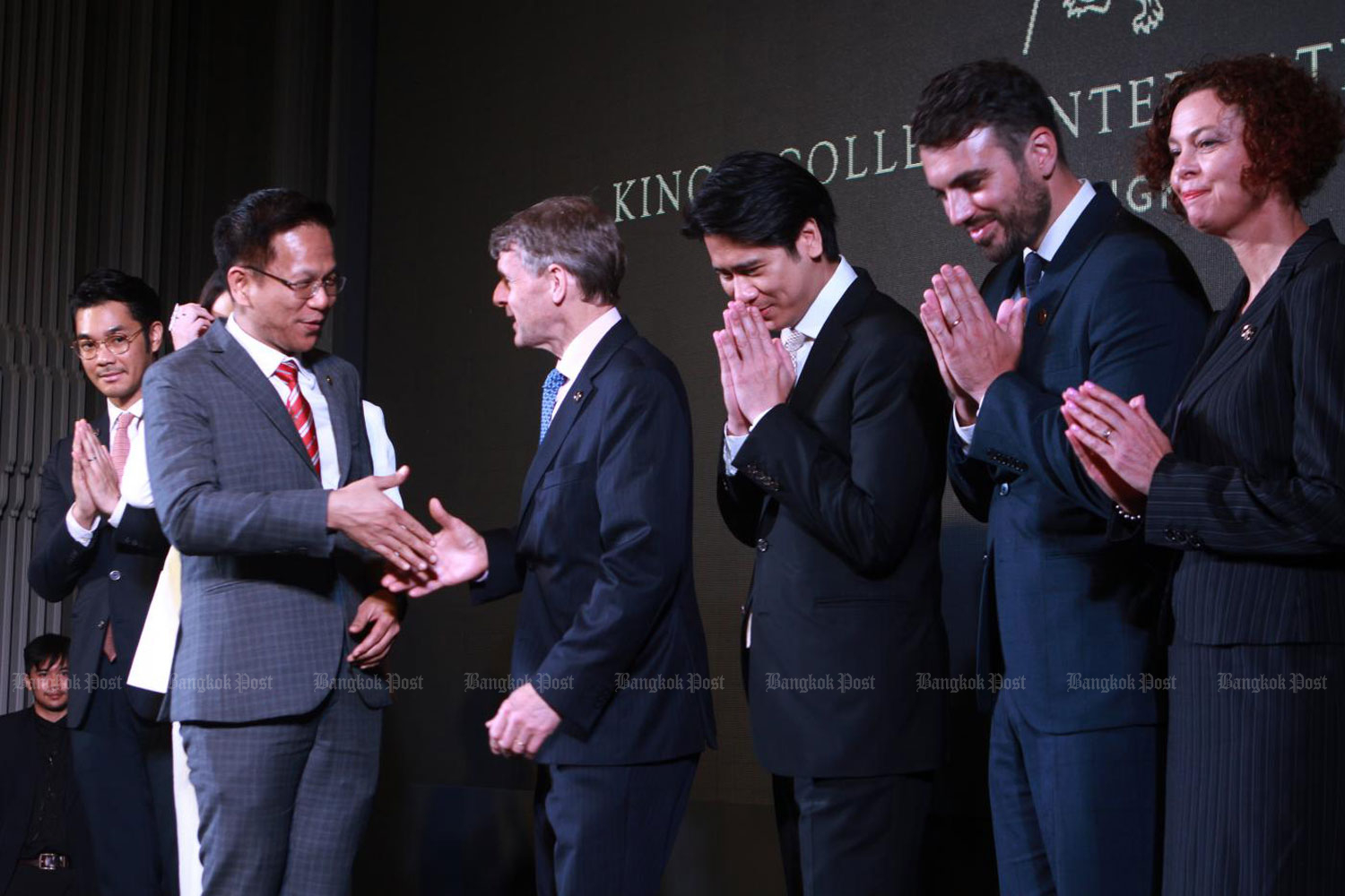 Prof Sakorn Suksriwong, president of Excellence Education Thailand, co-founder of King's Bangkok, shakes hands with Andrew Halls, King's College School Wimbledon headmaster and school executives on Friday.Pawat Laupaisarntaksin