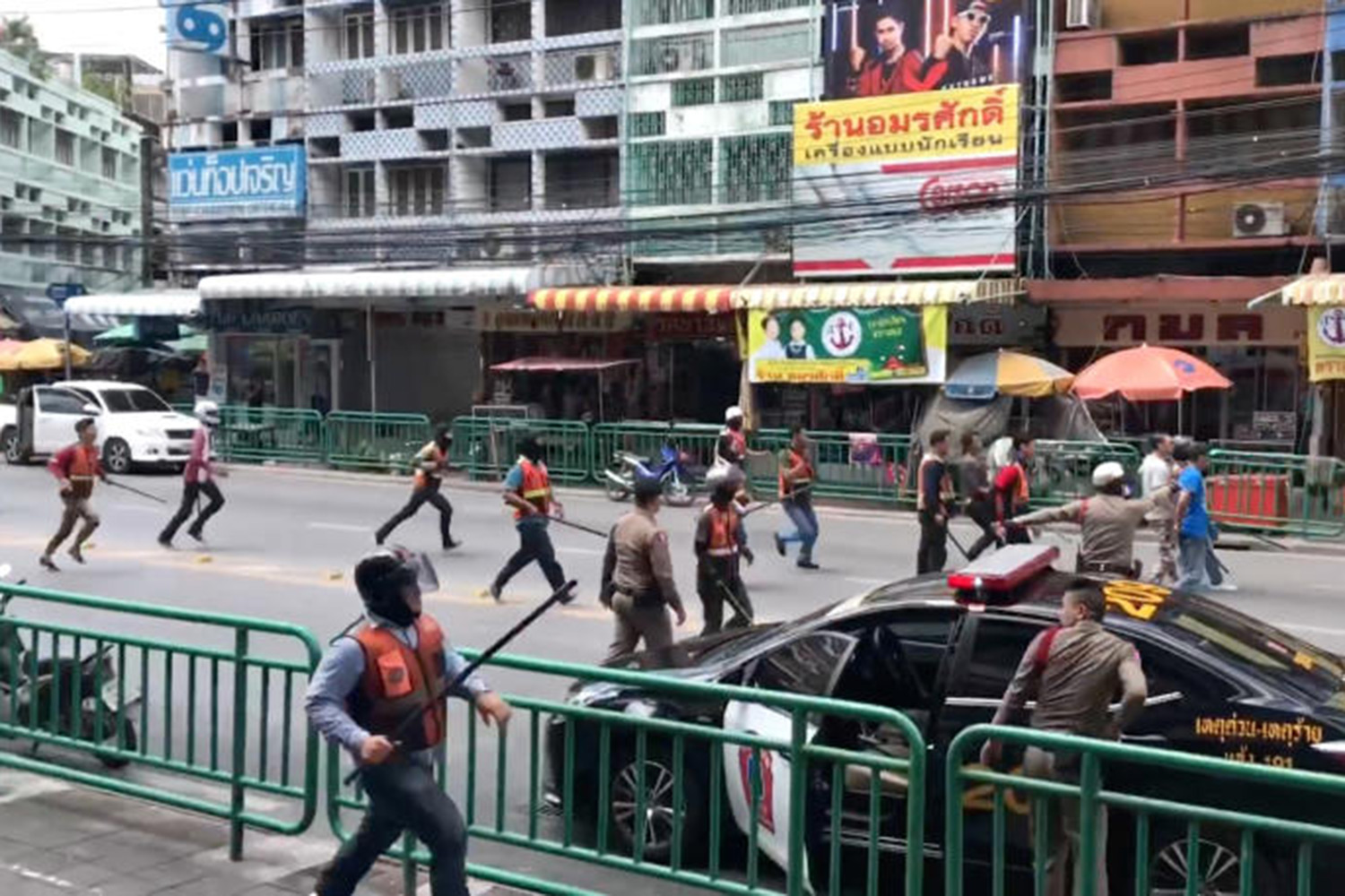 Police officers arrive to break up a violent brawl between members of two rival motorcycle-taxi queues on Sukhumvit Soi 103/1-2 in Bang Na district of Bangkok on Saturday morning. (Screen capture from clip by Salonaio Chakonkun Facebook page)