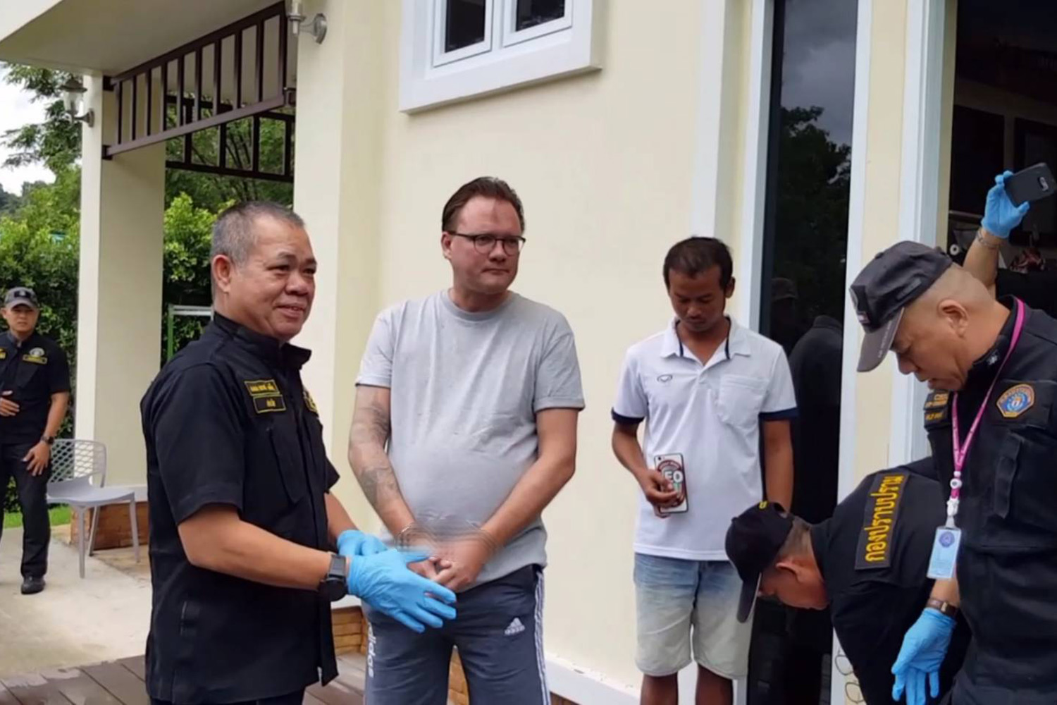 Crime Suppression Division police arrest Roger Nils-Jonas Karlsson (second from left), 45, a Swedish national, at a house on Koh Chang in Trat province. He was wanted by Interpol for money laundering over a virtual-currency investment scam in the US. (Photo supplied by Wassayos Ngamkham)