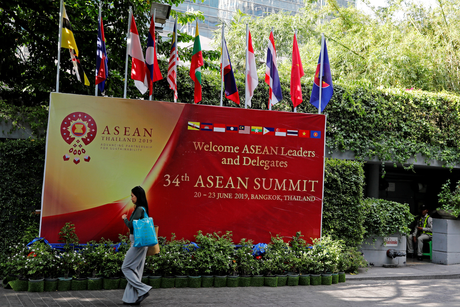 A woman walks past a banner at the venue of the Asean summit in Bangkok on Friday. (Reuters Photo)