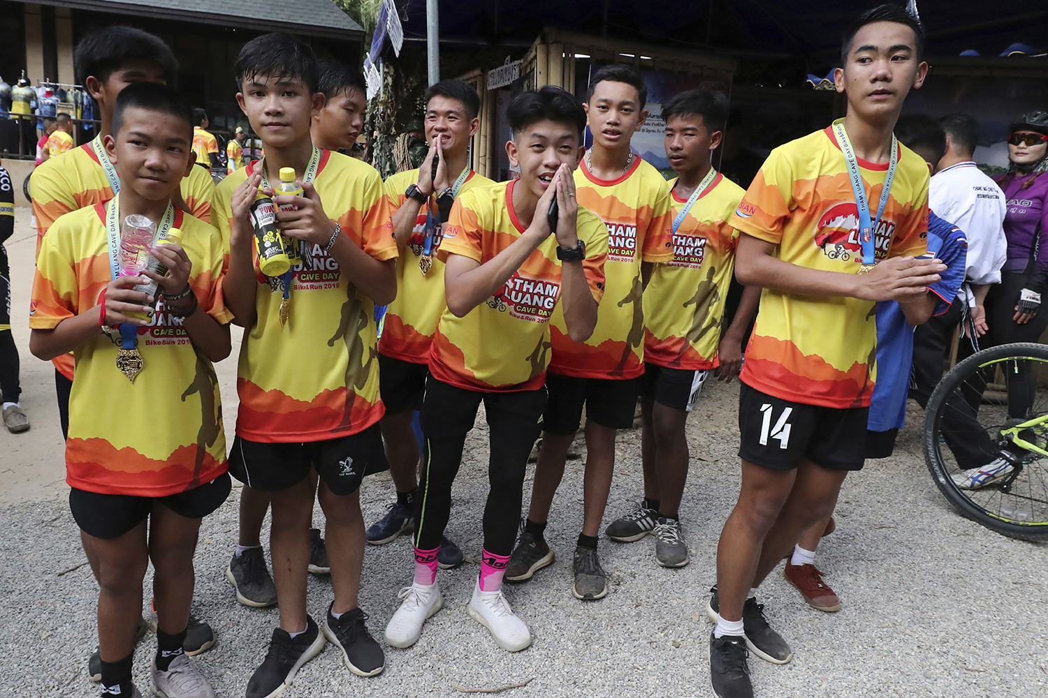 Members of the Wild Boars football team rescued from the Tham Luang flooded cave in Mae Sai district of Chiang Rai last year pose for the media after a marathon and biking event on Sunday. (AP photo)