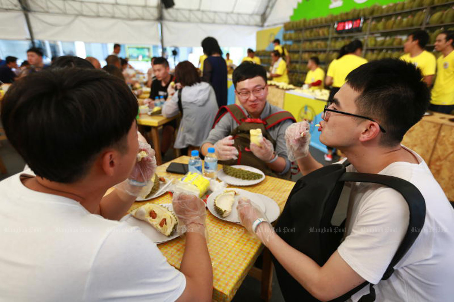 Tourists enjoy durian at the Thailand Fruit Festival 2019 at the CentralWorld shopping centre in Bangkok last month. The Tourism Council of Thailand expects the number of visitors to increase 4.65% this year to 40.06 million. (Photo by Somchai Poomlard)