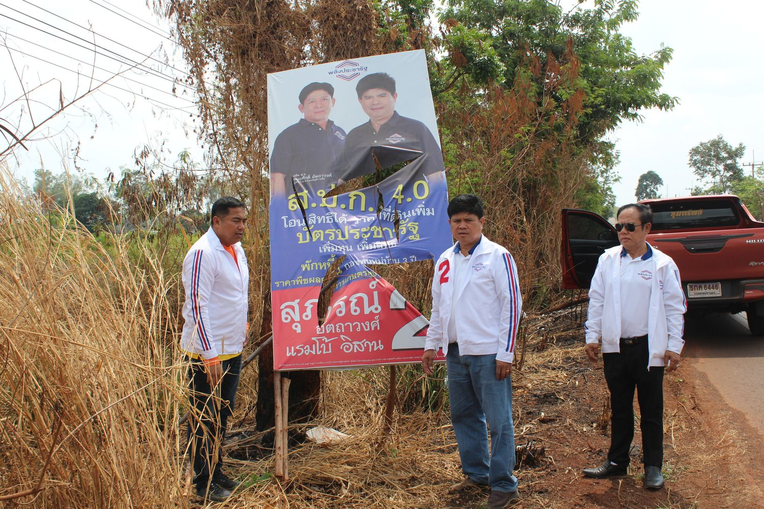 Suporn Atthawong (centre) shows one of his damaged election campaign posters in Nakhon Ratchasima on Feb 24 this year. He asked police to take legal action against the vandals. (Photo by Prasit Tangprasert)