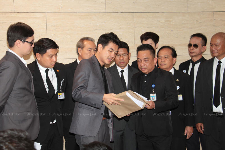 Future Forward Party secretary-general Piyabutr Saengkanokkul, centre left, files a petition on MPs' alleged media shareholding, at the parliament in Bangkok on June 4. (Photo by Tawatchai Kemgumnerd)