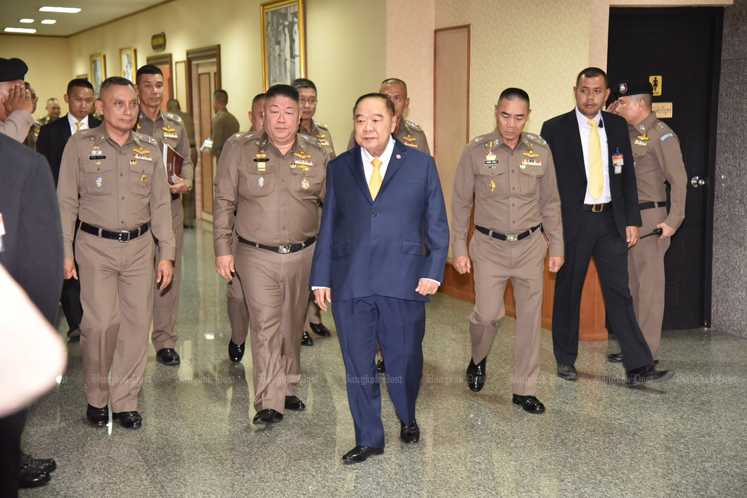 Deputy Prime Minister Gen Prawit Wongsuwon, centre, emerges from a meeting of the Police Commission on Wednesday with national police chief Pol Gen Chakthip Chaijinda, third from right, and Pol Gen Wirachai Songmetta, deputy national police chief, left. (Photo by Wassana Nanuam)
