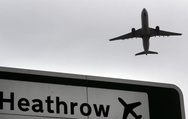 A plane takes off over a road sign near Heathrow Airport in London. (AP photo)