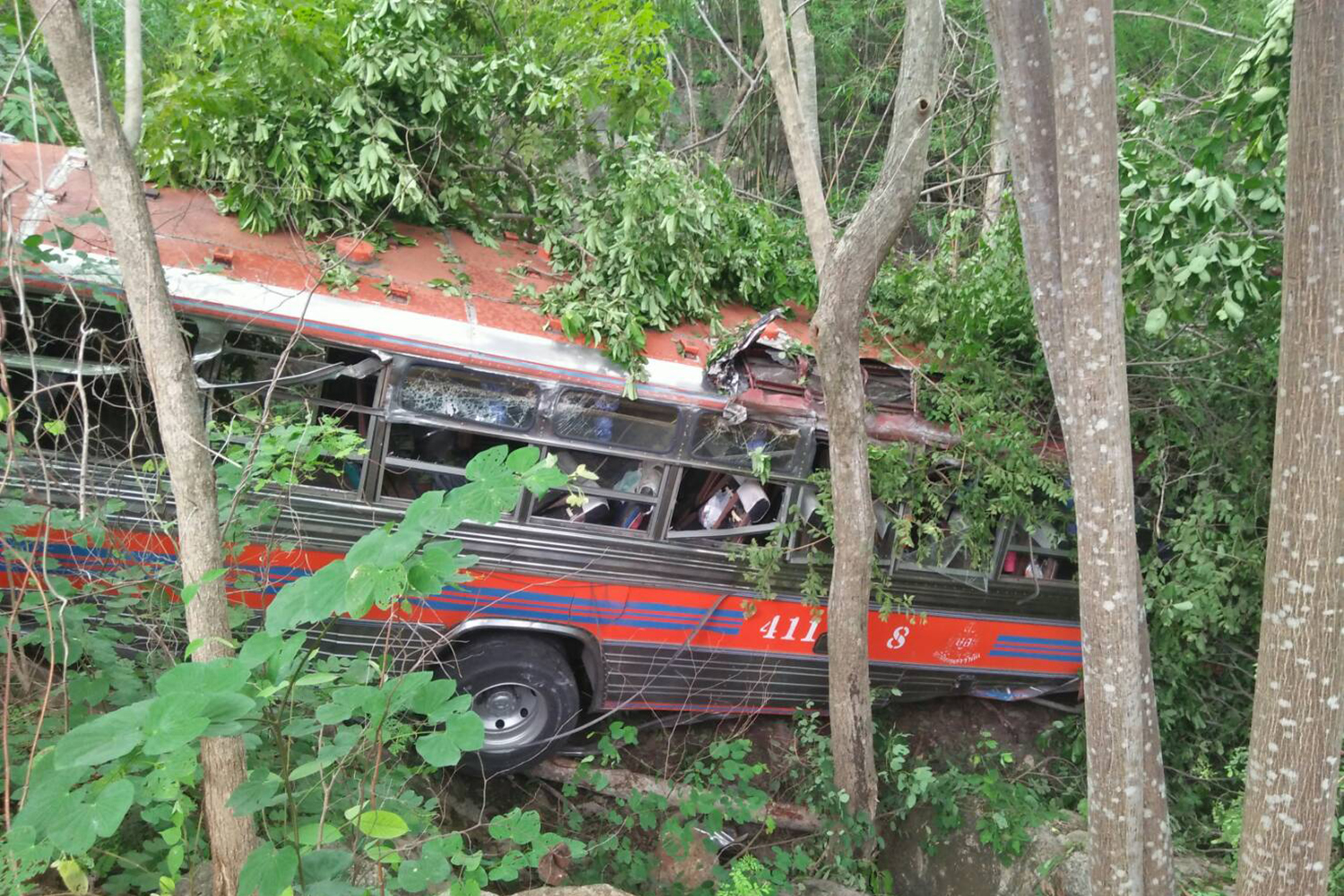 The crashed bus rests in a ditch after running off the road in Sai Yok district of Kanchanaburi, injuring about 30 people, on Thursday. (Photo by Piyarach Chongcharoen)