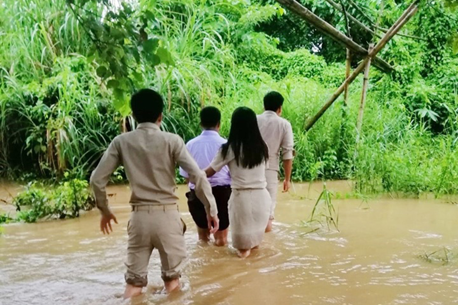 Thanoksak, a 16-year-old ethnic Karen student, leads teachers across the creek he has to wade each day to get catch a bus to school from his remote community in Sai Yok district, Kanchanaburi. (Photo by Piyarat Chongcharoen)