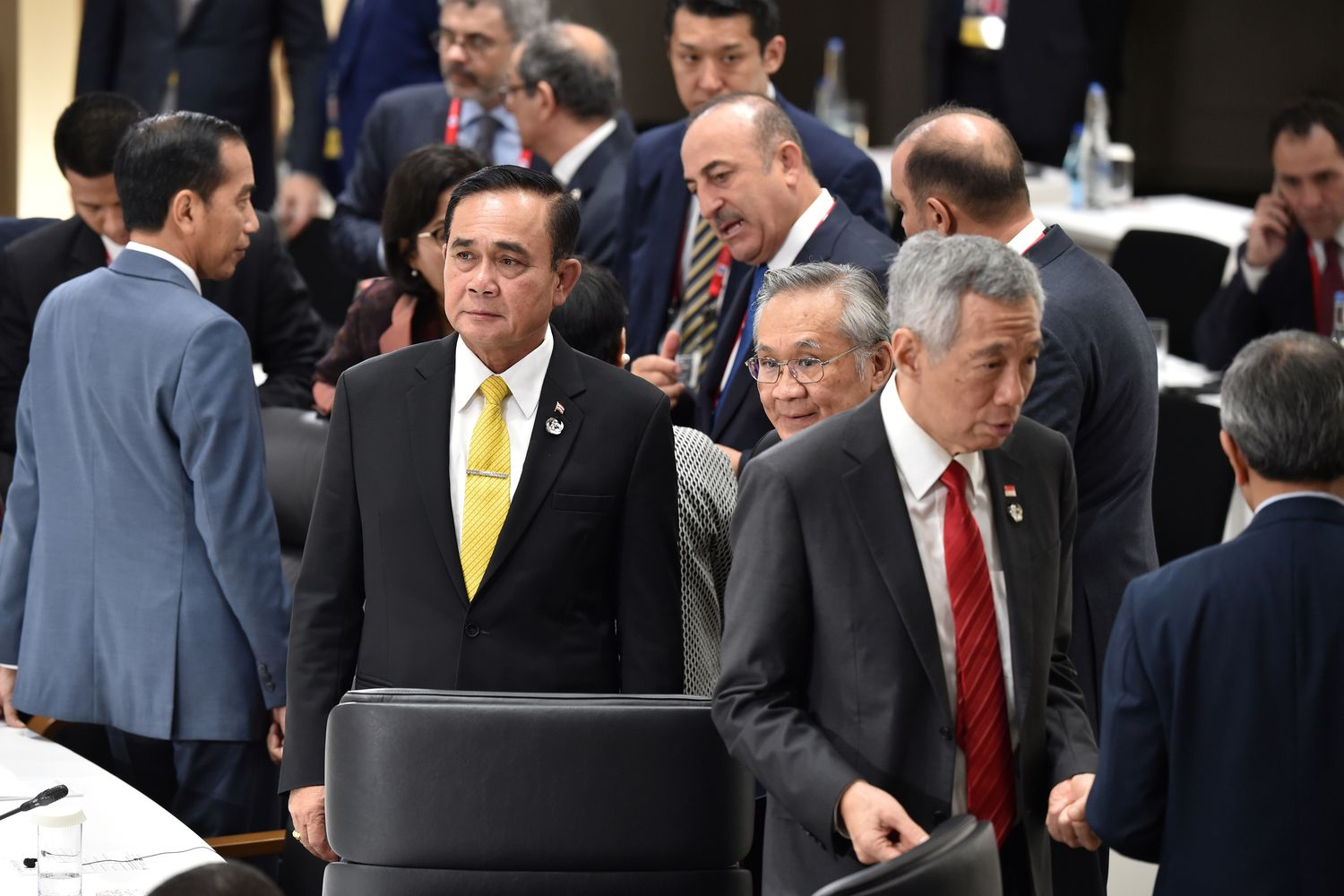 Prime Minister Prayut Chan-o-cha and Foreign Minister Don Pramudwinai (third from left) wait for the start of a session on women's workforce participation and ageing societies at the G20 Summit in Osaka on Saturday. Also attending the session were Indonesian President Joko Widodo (left) and Singapore Prime Minister Lee Hsien Loong (second from right). (Kazuhiro Nogi/Pool via Reuters)