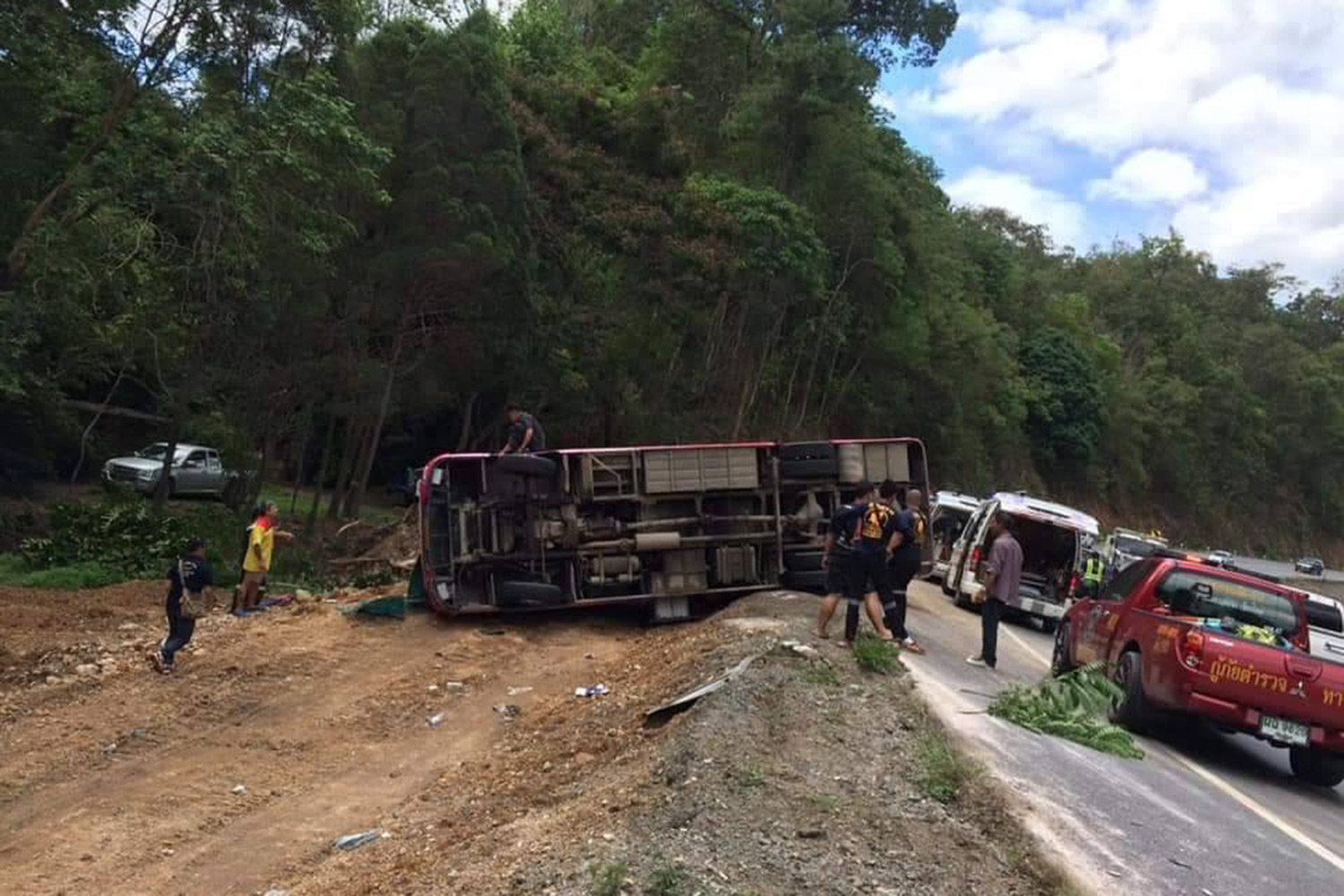 Rescue workers come to the aid of injured passengers from an overturned tour bus in Doi Saket district of Chiang Mai on Saturday afternoon. (Photo from Ruamduaychuaykan Facebook page)
