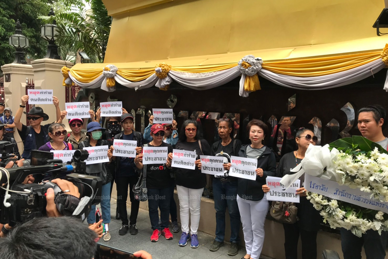 Black-clad activists hold signs attacking those who assault people with different political views, as they gather at the Royal Thai Police Office on Tuesday to present a wreath signifying the failure of the justice system.  (Photo by Wassayos Ngamkham)