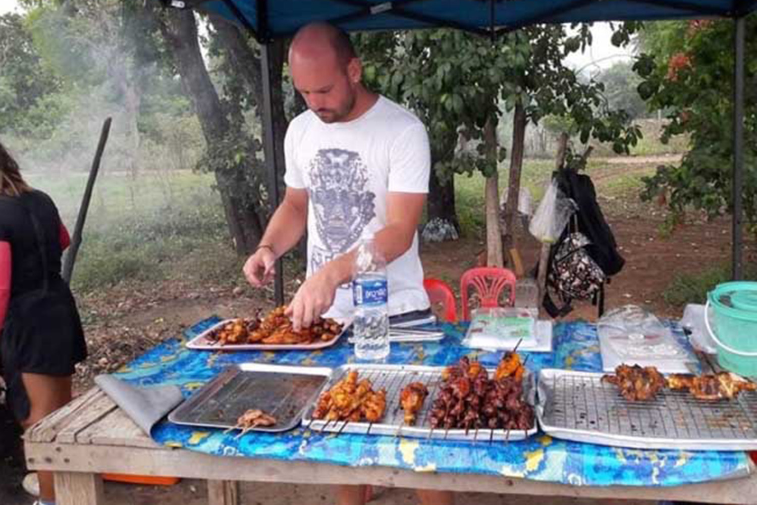German national Maximilian Fernsebner, 34, won praise on social media after images showing him helping his Thai wife sell grilled chicken in Pak Chong district, Nakhon Ratchasima, went viral online. His instant popularity drew the attention of police, who learned he is wanted on an Interpol red notice. He is now awaiting deportation to Germany to stand trial. (Supplied photo via Wassayos Ngamkham)