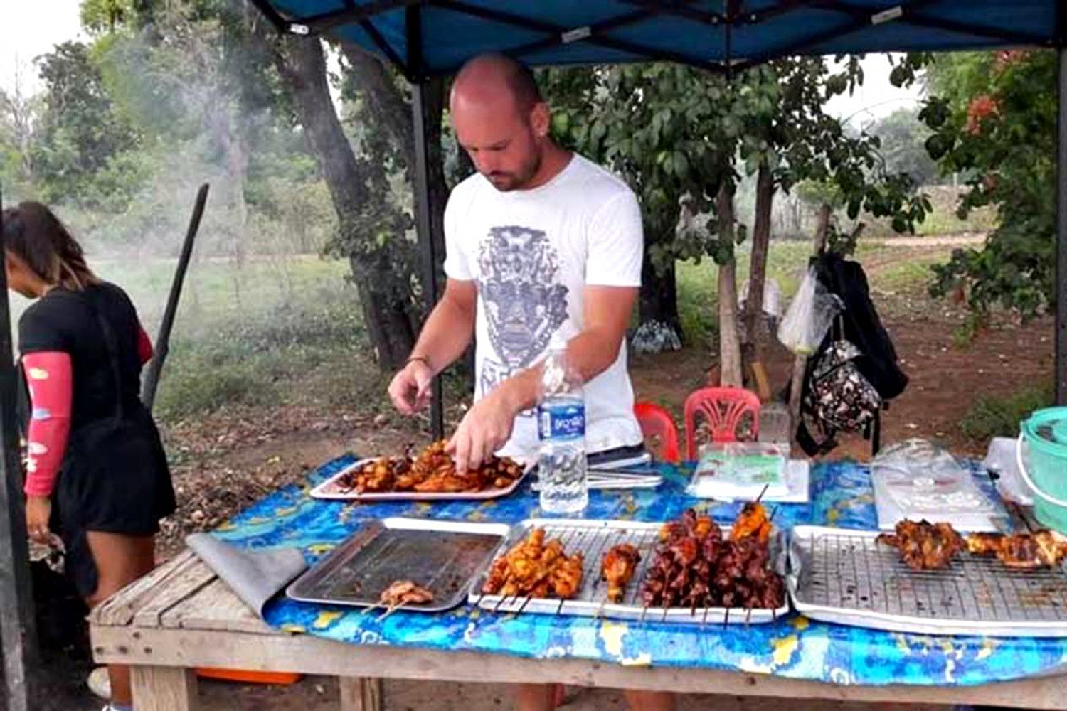 German national Maximilian Fernsebner, 34, helps his Thai wife sell grilled chicken in Pak Chong district of Nakhon Ratchasima.  immigration police photo