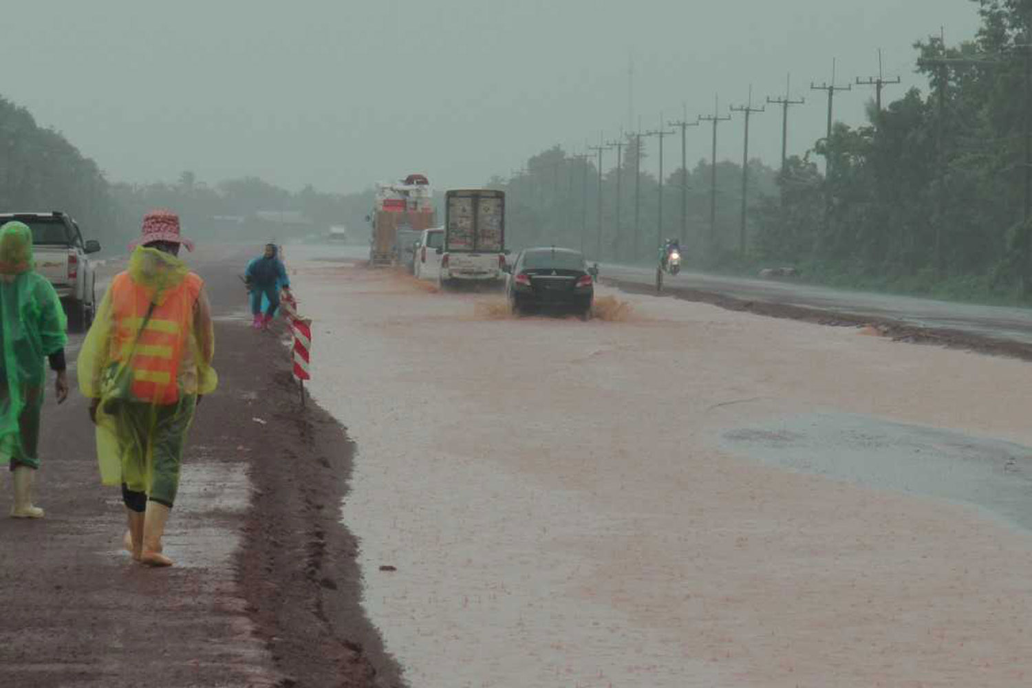Flooding further hinders vehicles as they pass roadworks on a highway in Pla Pak district of Nakhon Phanom province on Wednesday. (Photo by Pattanapong Sripiachai)