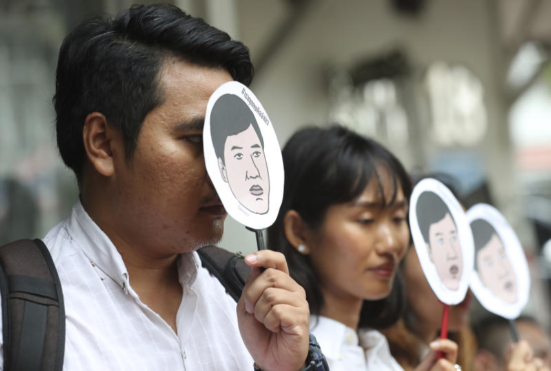 Human rights activists for Amnesty International hold masks of Thai pro-democracy leader Sirawith Seritiwat during a protest at police headquarters in Bangkok on Wednesday. (AP photo)