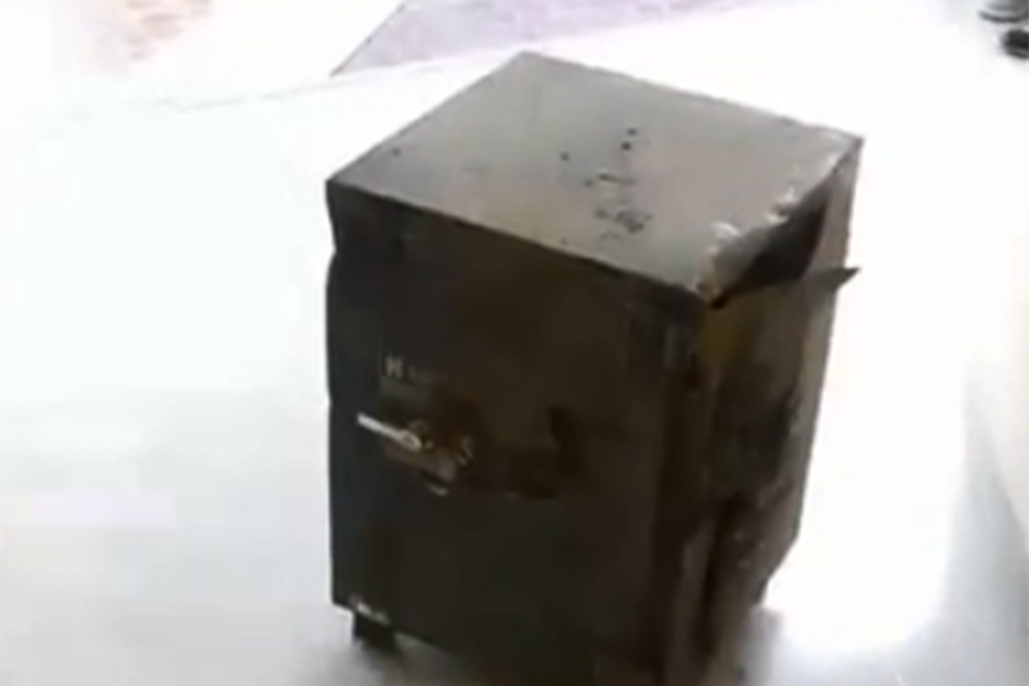 A heavy safe containing 17 million baht worth of valuable items and cash is retrieved from three men allegedly involved in the theft of a biomolecular therapy centre on Rama II Road in Bangkok. (Screen capture from TV channel 7)