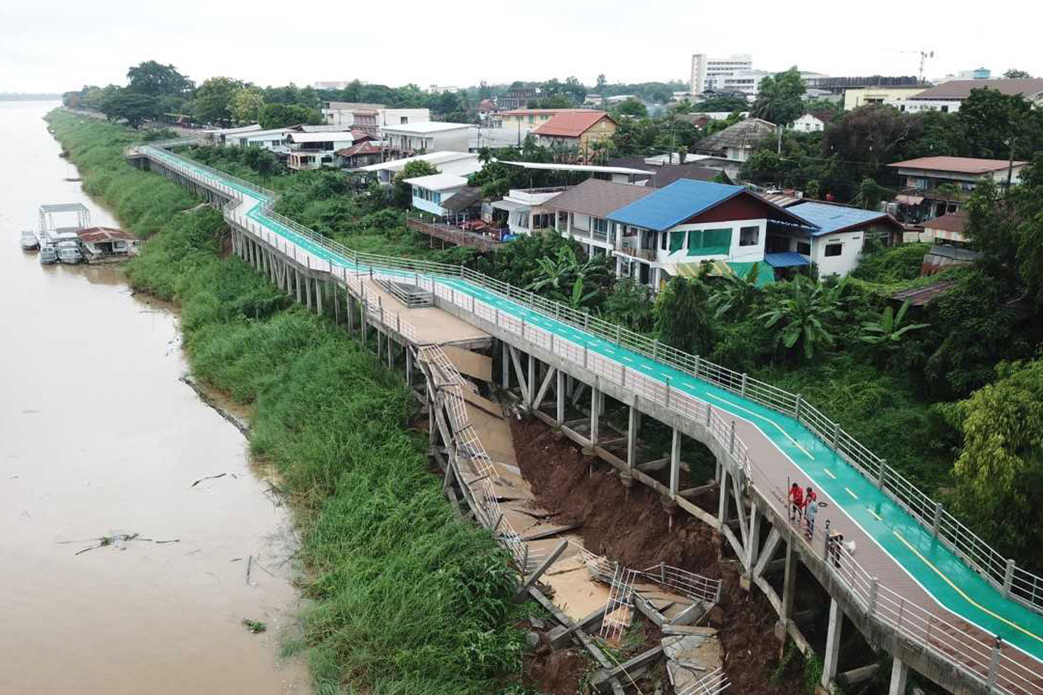 The viewpoint section of a new cycling path alongside the Mekong river collapsed, in Muang district of Nakhon Phanom province, on Tuesday. State engineers deemed the cycling path unsafe and have closed it. (Photo by Pattanapong Sripiachai)