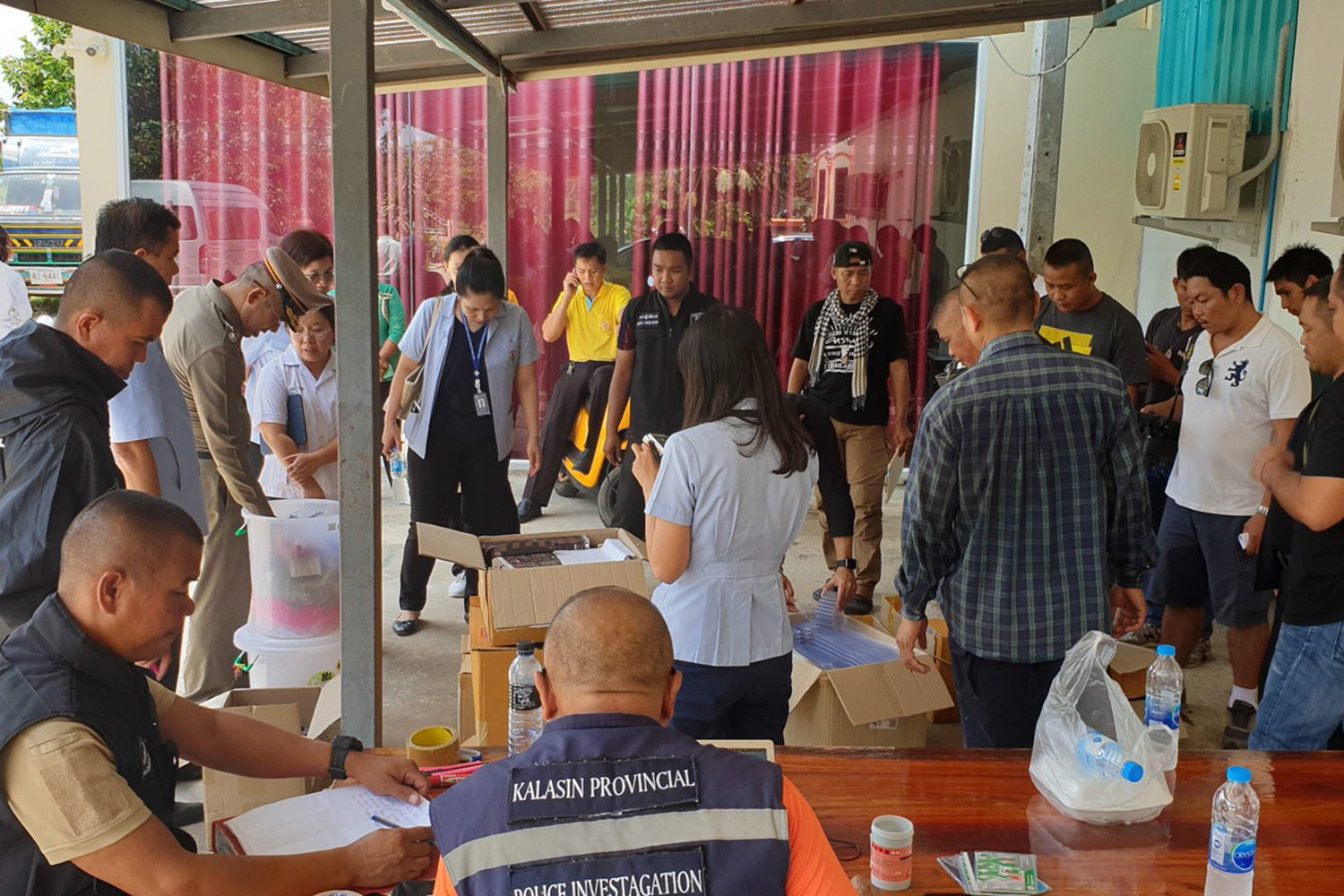 Investigators gather at the Kalasin property that housed a factory making unapproved weight-loss capsules, which have been linked to the death of one woman. (Photo by Yongyuth Phuphuangpet)