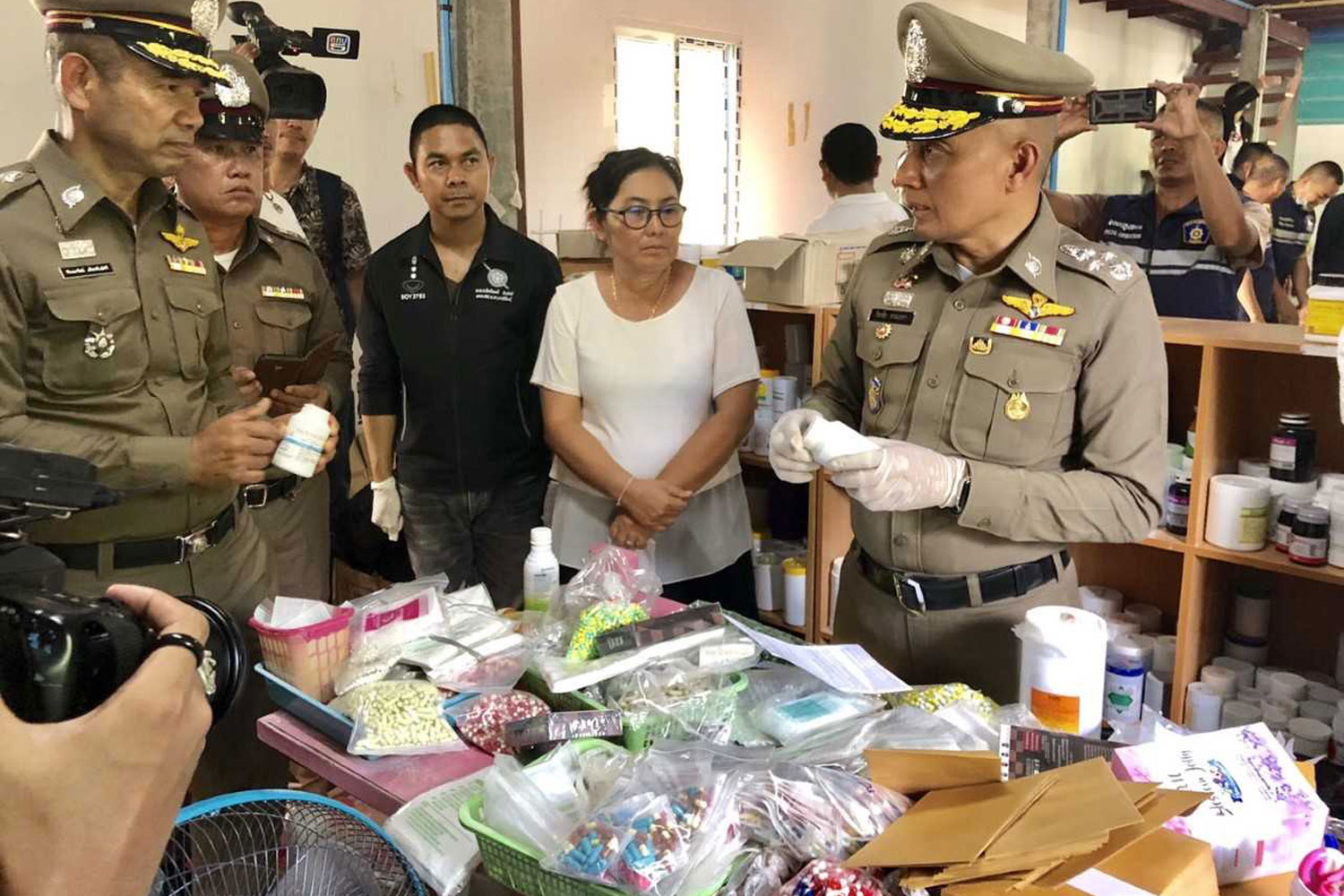 Police examine quantities of weight-loss drugs found illegally produced at the house of suspect Wassapassorn Sulamnat, 52, in Kalasin's Na Mon district on Saturday. They raided two warehouses and seized more than 1 million weight-loss capsules. (Photo by Yongyuth Phuphuangpet)