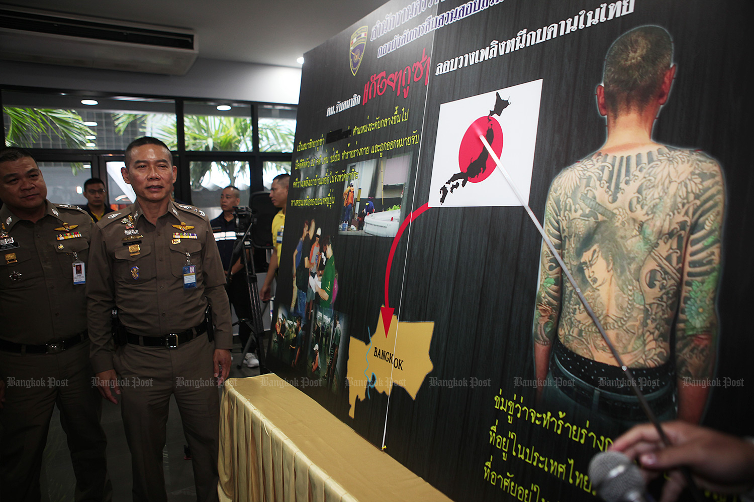 Immigration police show a chart detailing the arrest of a Yakuza gangster for alleged extortion. Katsuhiko Yamazaki, 62, was detained in Phra Nakhon district last Wednesday. (Photo by Apichart Jinakul)