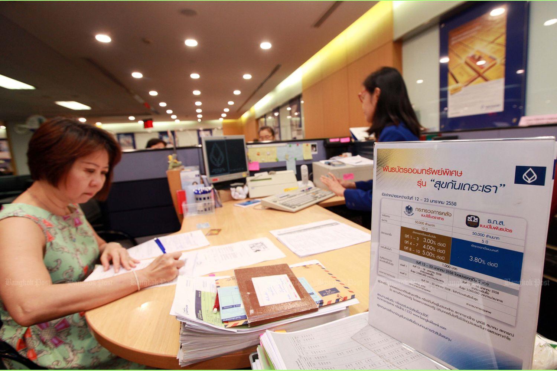 A woman fills a form to buy a government savings bond at a bank branch in Bangkok. (Bangkok Post file phgoto)