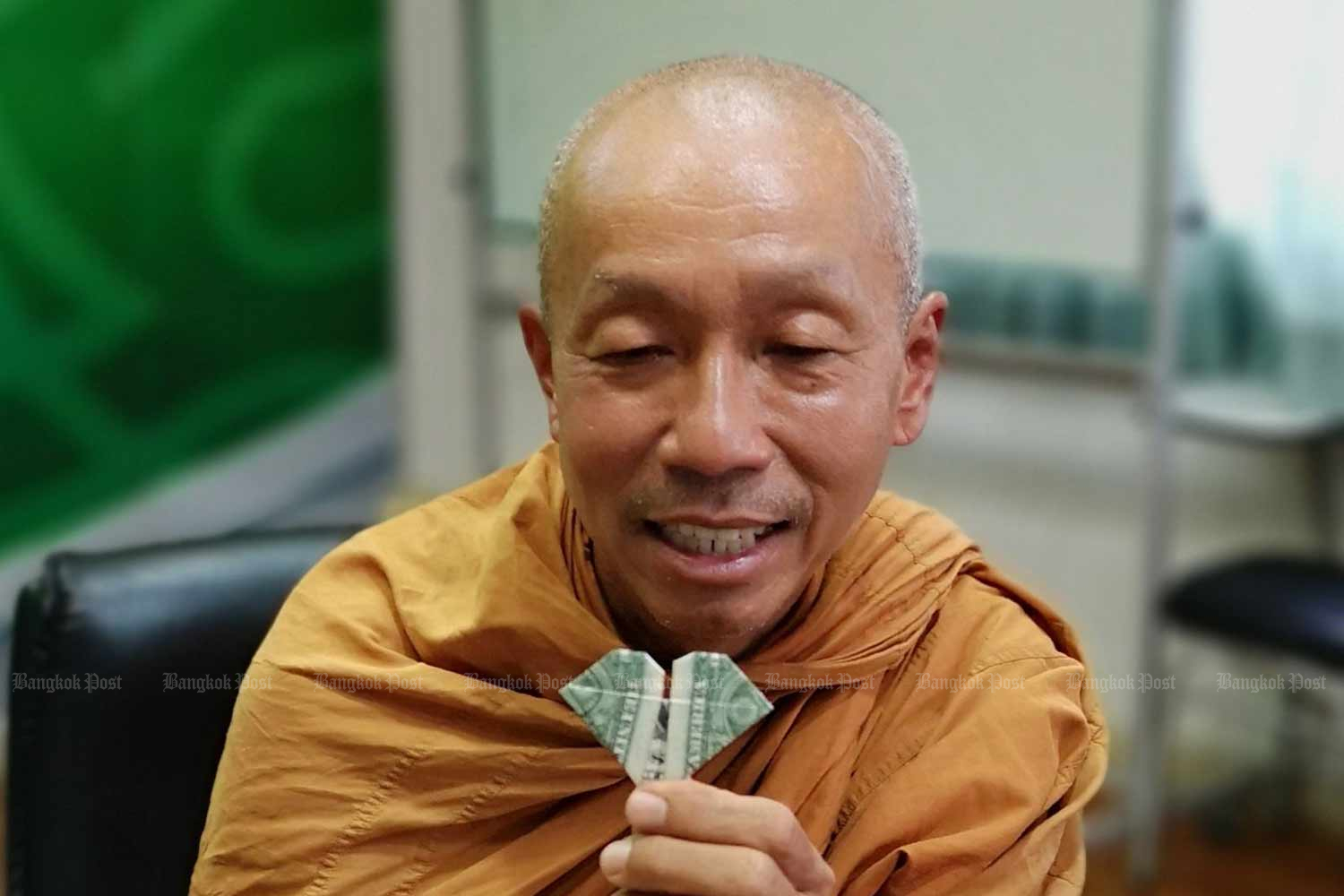 Phra Sutham Nateetong shows a one-dollar banknote folded into a heart shape he received from a resident in New Mexico as a souvenir. He passed on this souvenir to the Thai Journalists Association in Bangkok where he visited on Thursday. (Photo by Kornchanok Raksaseri)