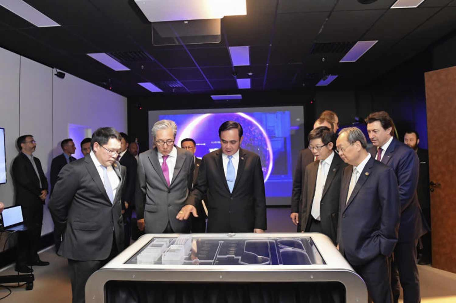 Prime Minister Prayut Chan-o-cha, centre, looks at the model of an aircraft maintenance centre planned for Rayong provinces' U-Tapao airport, in France last year. (Government House photo)