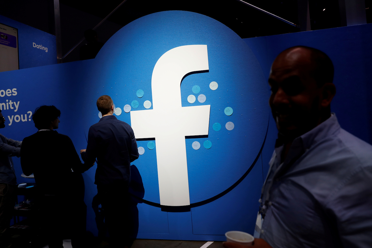 Attendees walk past a Facebook logo during a developers' conference held by the company in San Jose, California in April. (Reuters Photo)