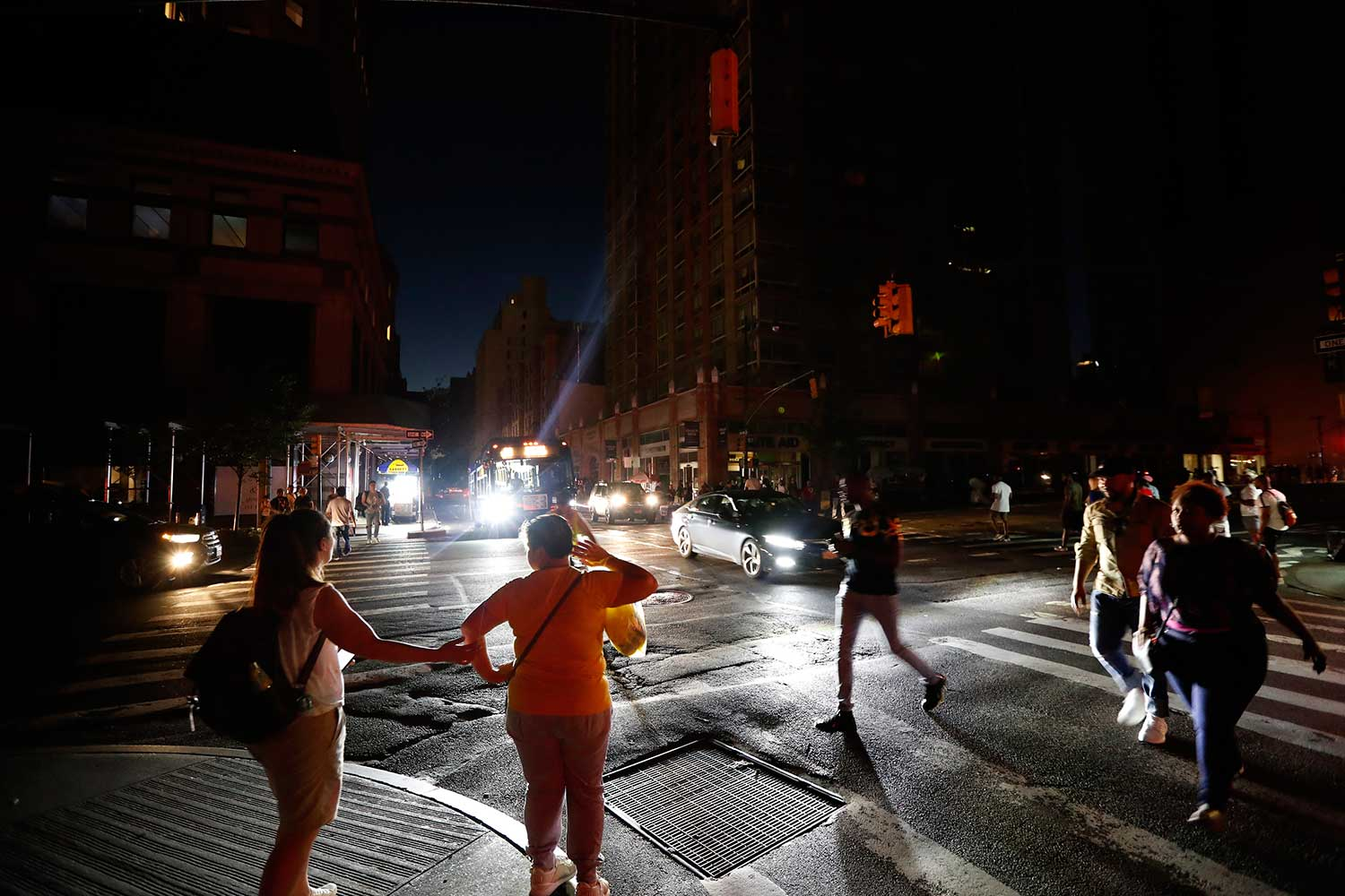 Pedestrians cross a dark street during a power outage on Saturday in New York. (AP photo)