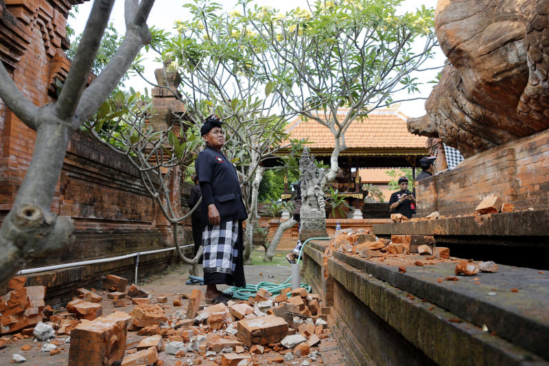 A Balinese man stands near a damaged temple in Bali, Indonesia on Tuesday. (AP photo)