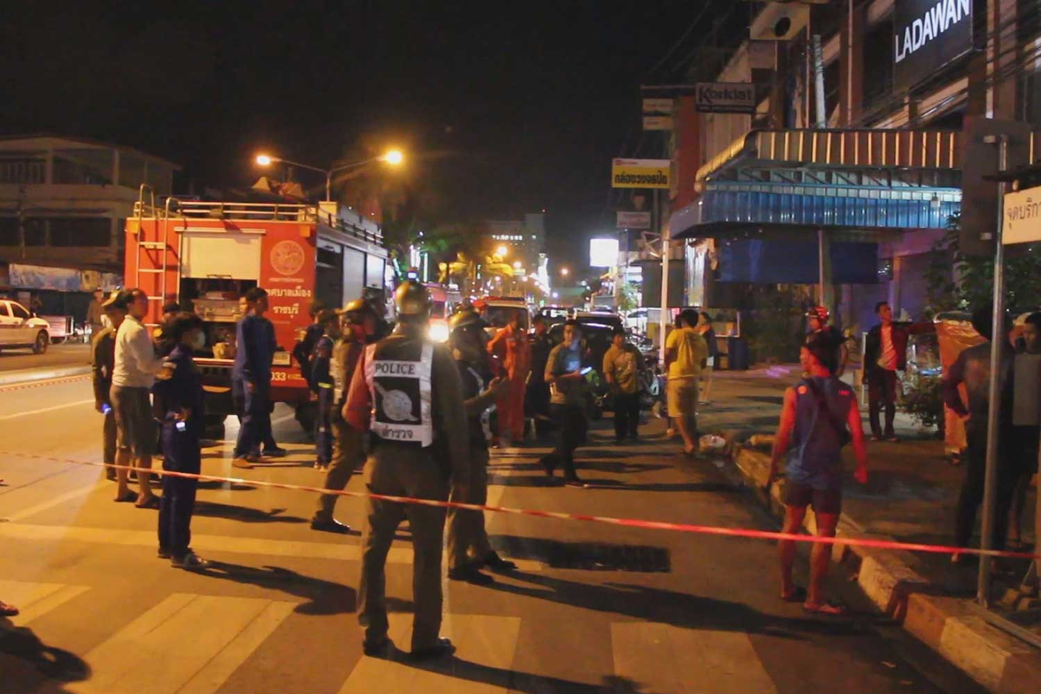 Police and rescue volunteers gather in front of a tutoring school in Muang district of Ratchaburi on Monday night as a woman employee threatens jump to her death. She was assisted to safety. (Photo taken by Saichon Srinuanchan)