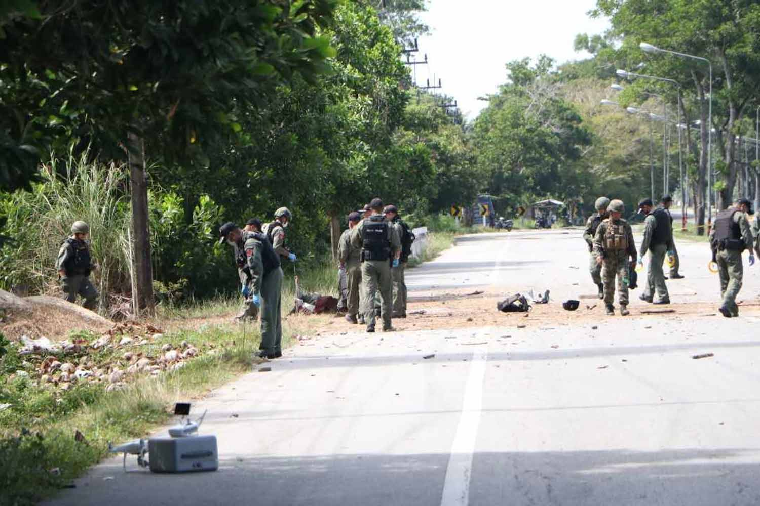 Bomb experts at the scene of the explosion on Phetkasem Highway in Bacho district of Narathiwat province on Wednesday morning. (Photo by Waedao Harai)
