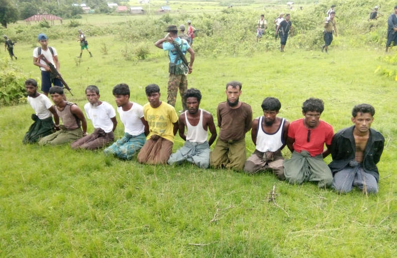 Ten Rohingya men with their hands bound kneel as members of the Myanmar security forces stand guard in Inn Din village of Rakhine State, Myanmar, Sept 2, 2017. All were later shot dead. (Reuters file photo)