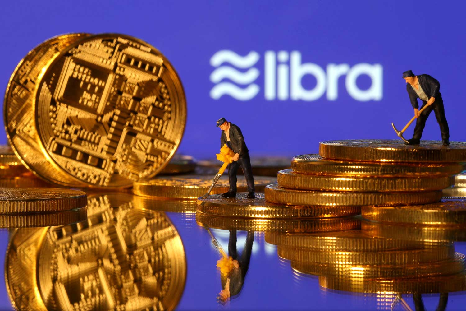 Small toy figures are seen on representations of virtual currency in front of the Libra logo in this illustration picture on June 21, 2019. (Reuters photo)