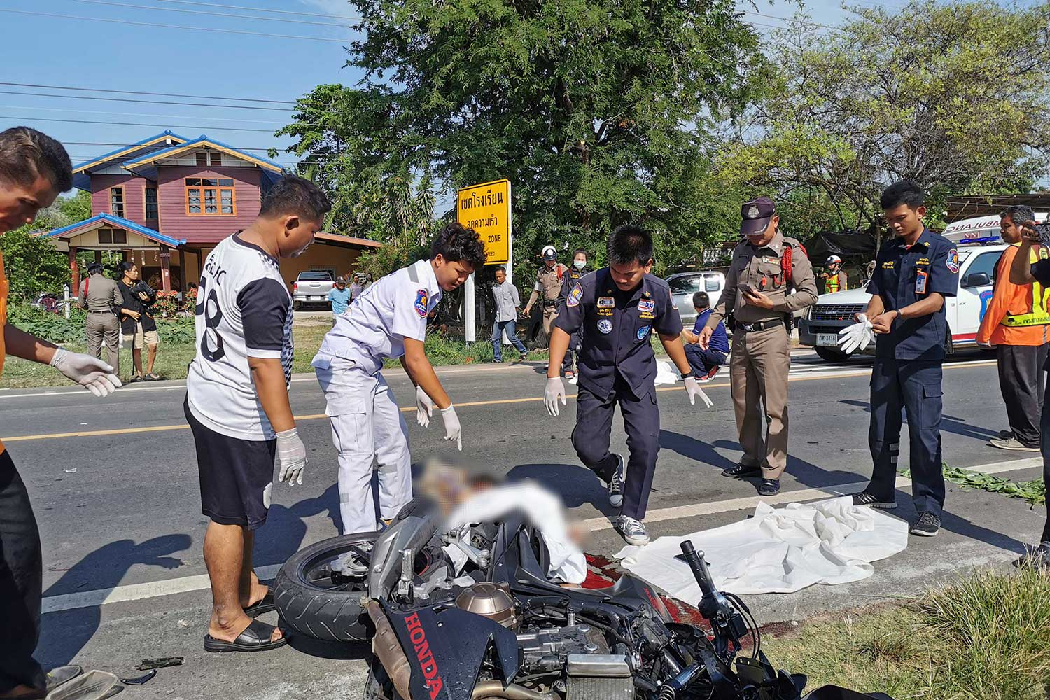 Rescue workers try to move the body of a 27-year-old man from the wreckage of his big bike while a 68-year-old man, rider of a motorcycle with his push cart tricycle involved in the crash, is found dead not far from the scene on Si Sa Ket-Kantharalak Road in Muang district, Si Sa Ket province, on Friday morning.
