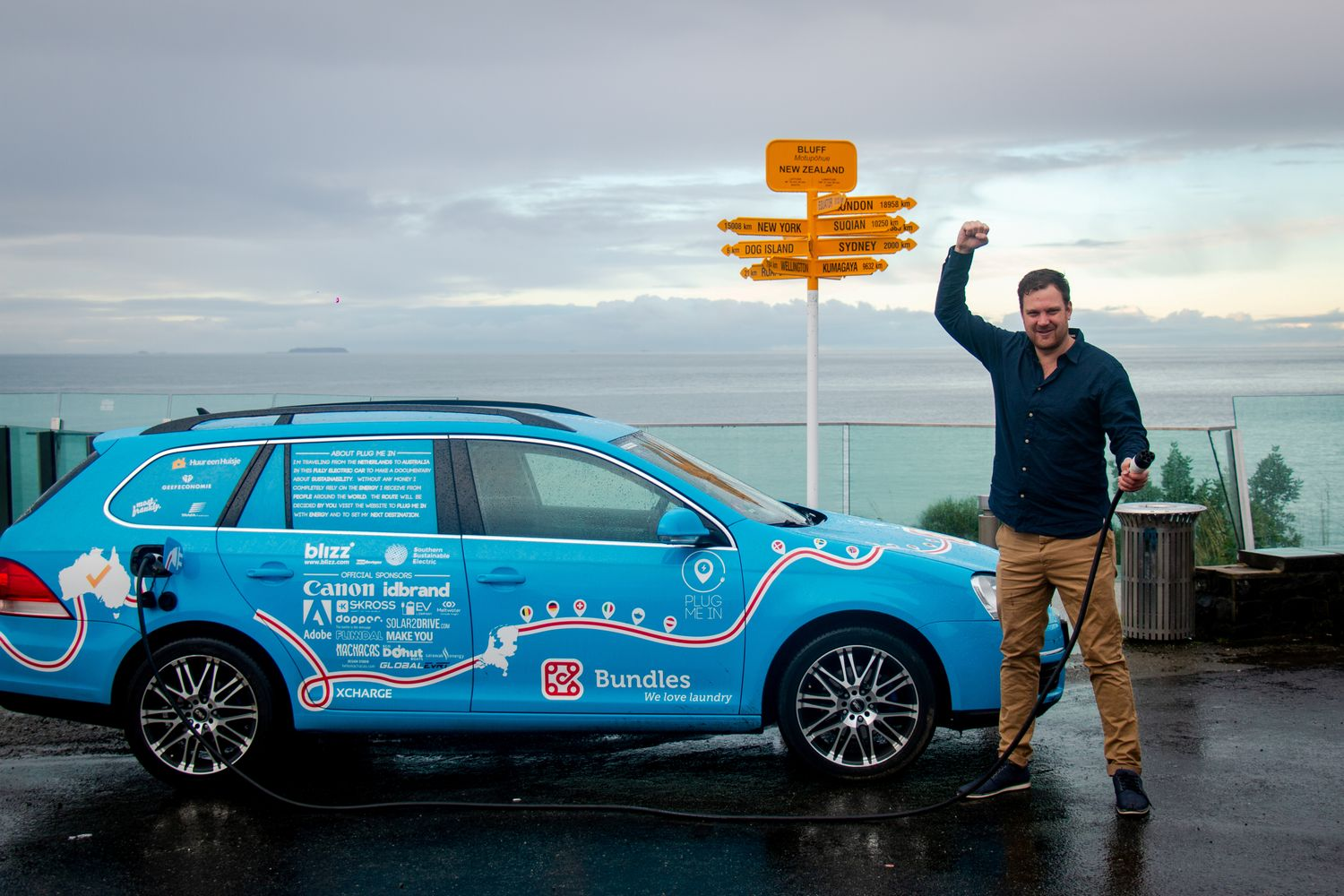 Dutchman Wiebe Wakker holds a charging cable as he poses with his electric vehicle, the Blue Bandit, after travelling 34 countries to reach Bluff, New Zealand's most southern tip, in this handout photo released on Friday. (Wiebe Wakker/Handout via Reuters)